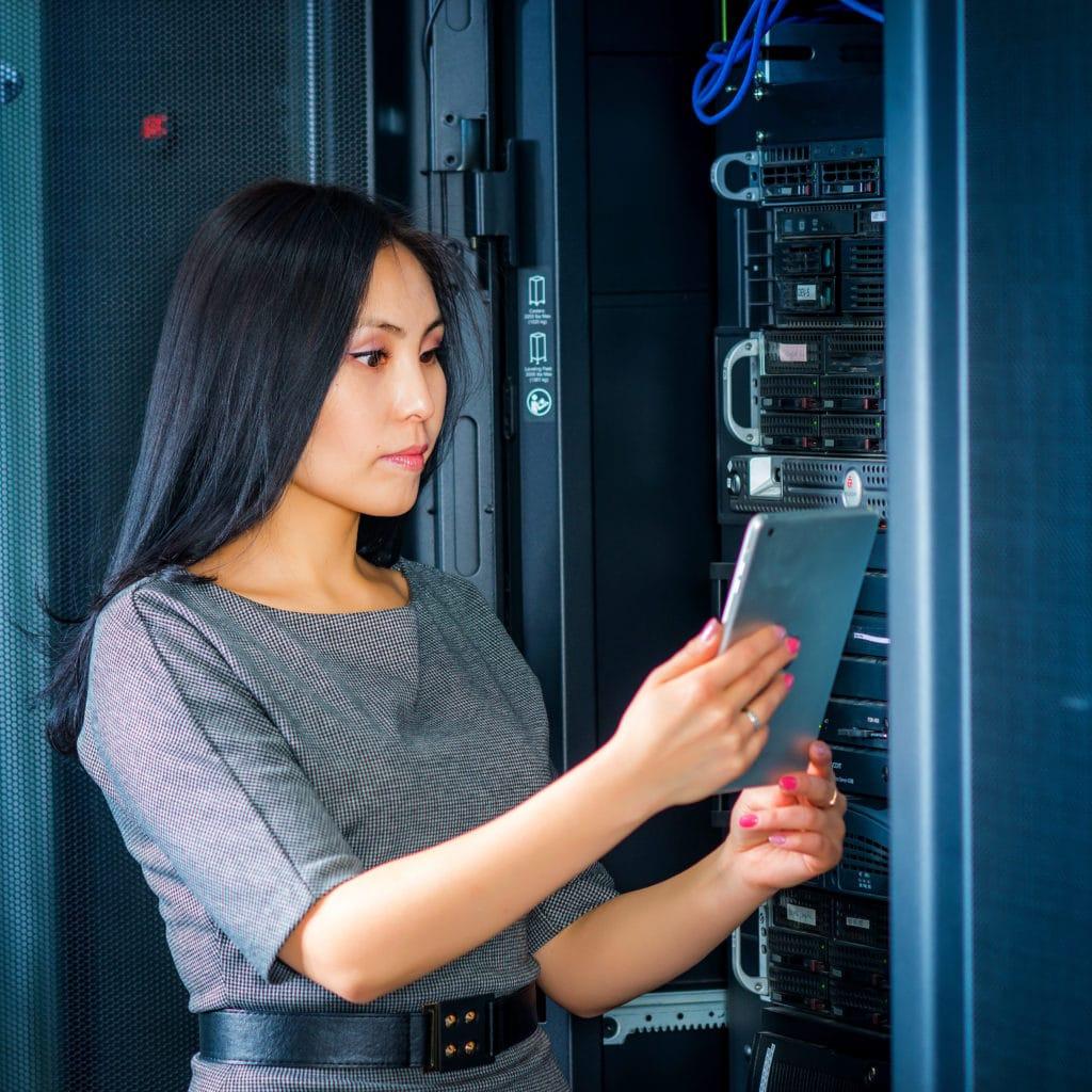 Empresaria joven ingeniero con tableta en la sala de servidores de red.