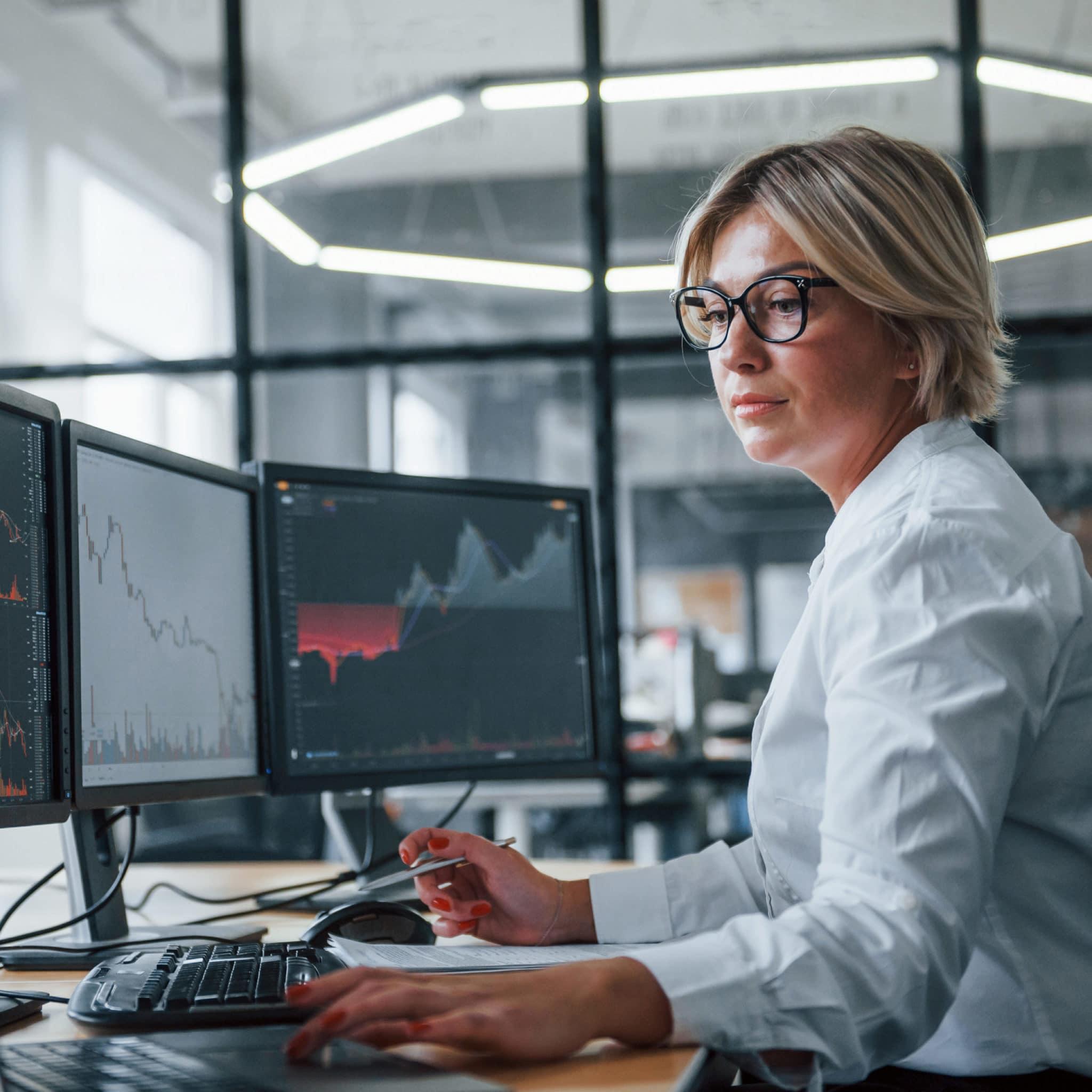 Female stockbroker wearing glasses working on laptop computer beside monitors displaying graphs.
