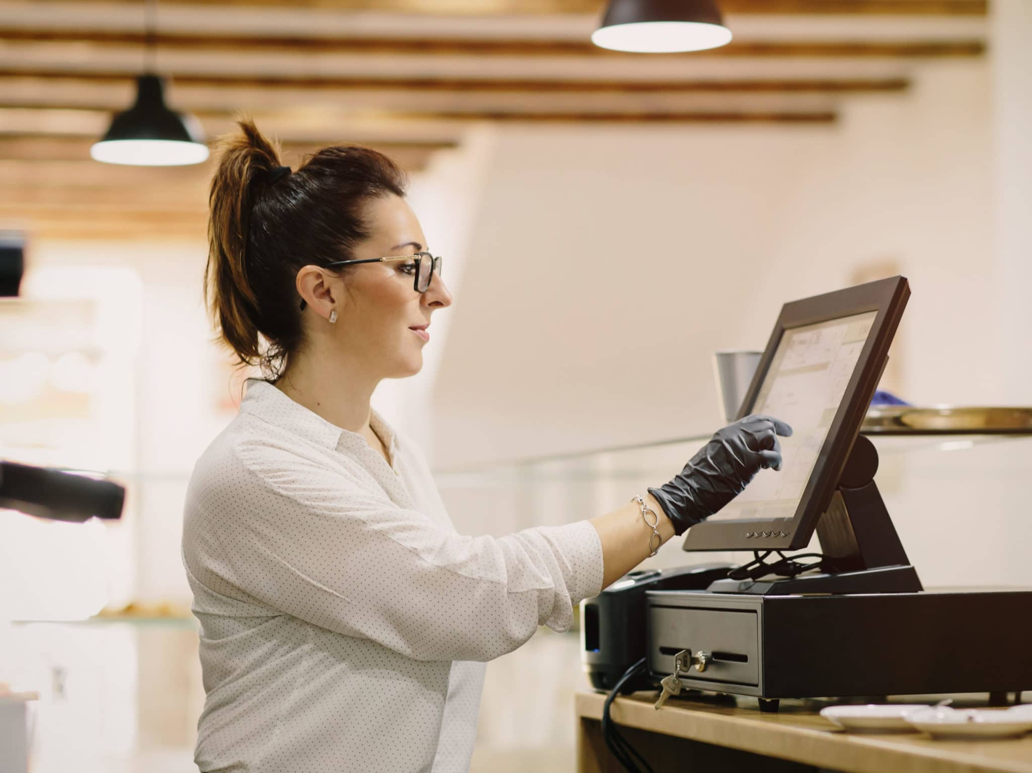Woman wearing glasses pressing buttons on POS machine in cafeteria.