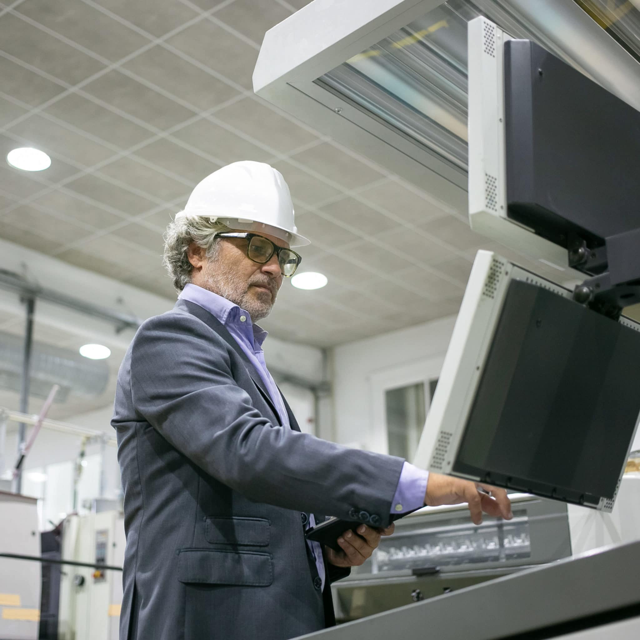 Male engineer with gray hair, wearing glasses and a hard hat, operating industrial machine.