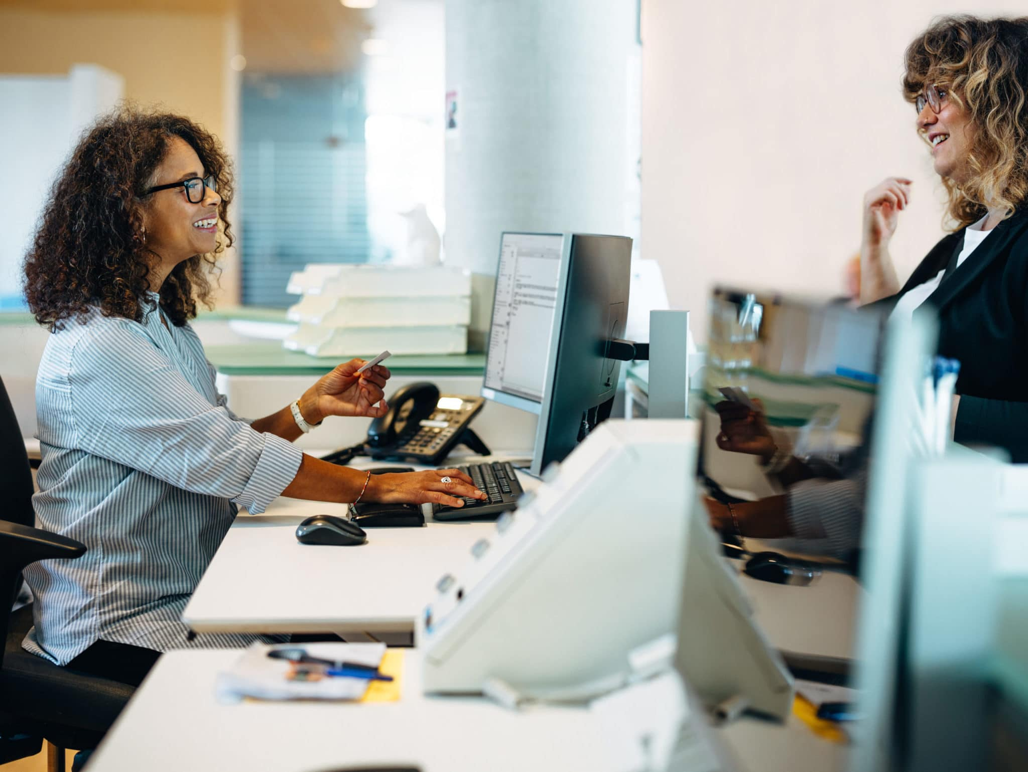 Woman office administrator sitting at desk and smiling while assisting a woman standing at her desk.