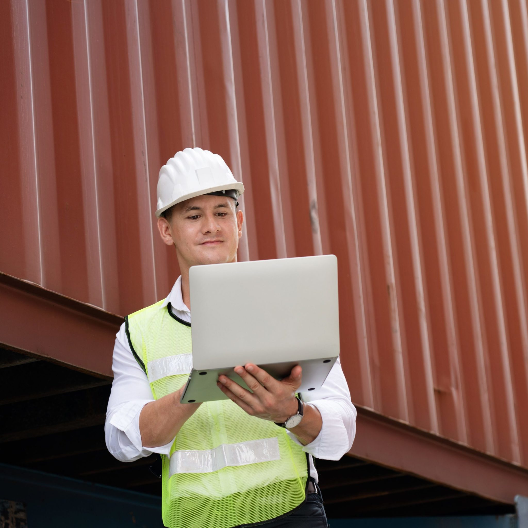 Male engineer in hardhat and reflective vest holding laptop computer and working on it.