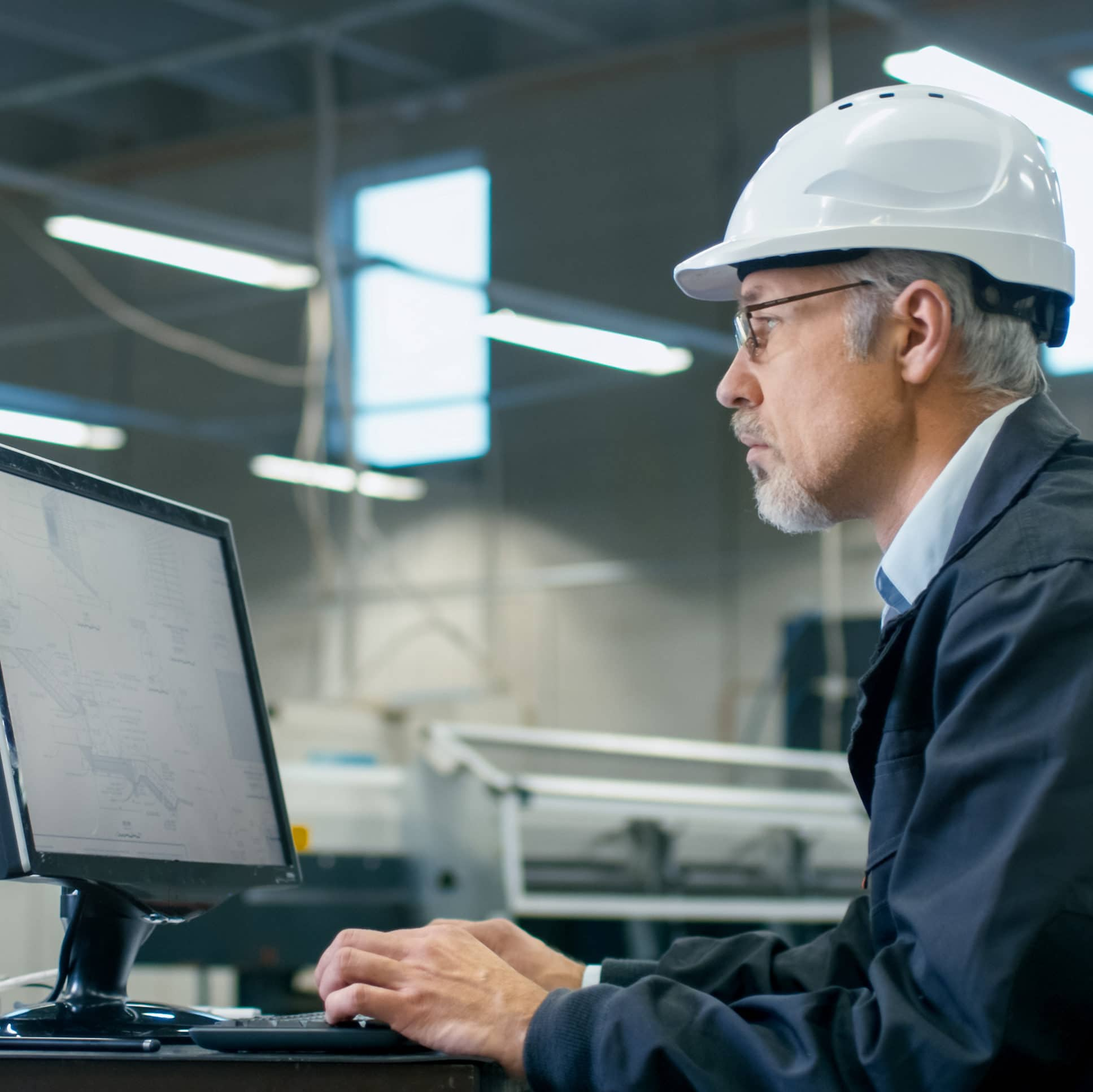 Engineer in hardhat and glasses working on a desktop computer.
