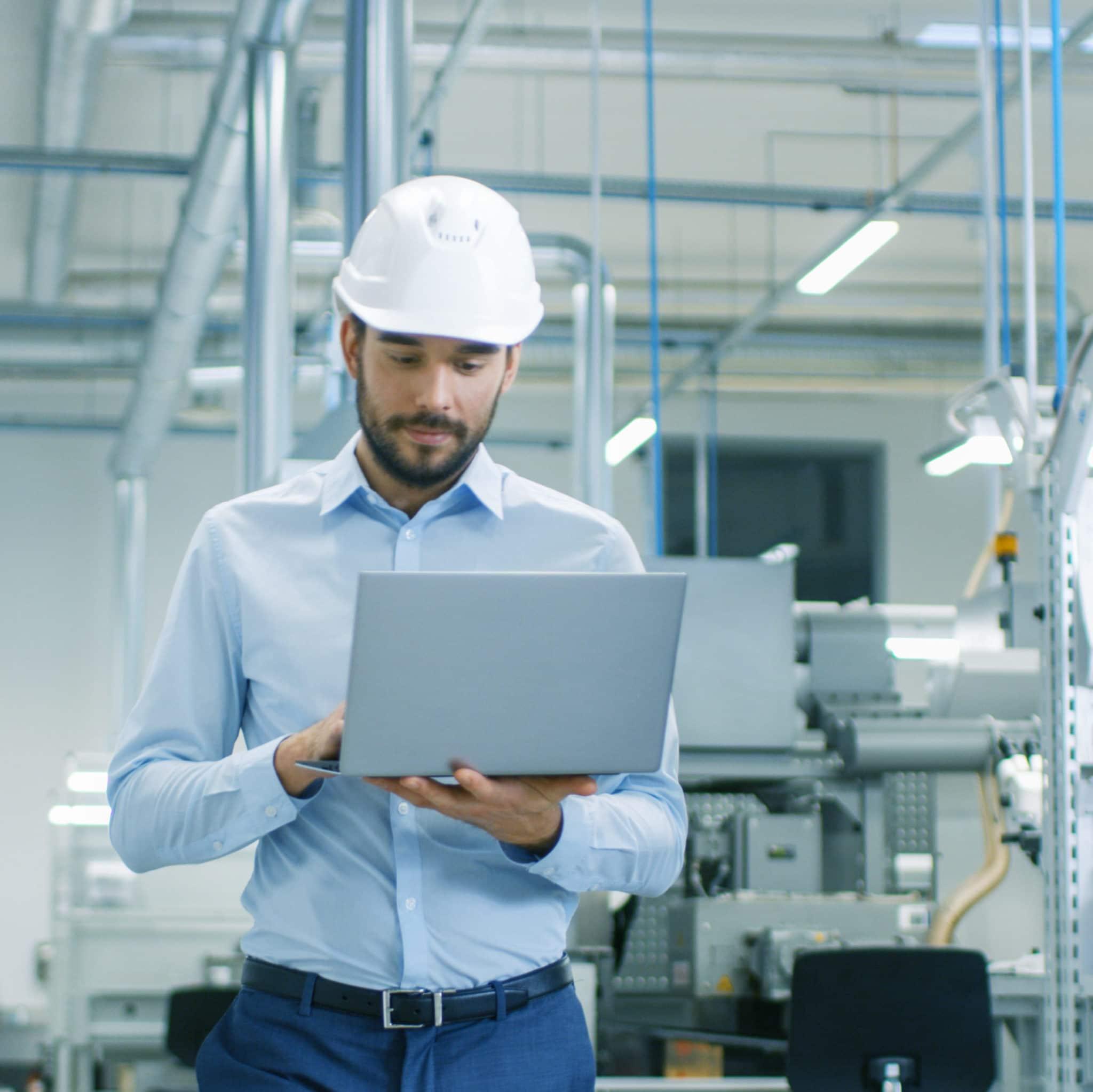 Male engineer wearing hard hat walking with laptop computer.